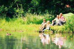 Familj av fyra som har rolig det fria i sommaren Arkivfoto