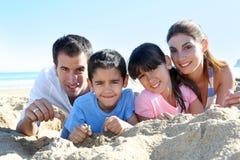 Familj av fyra som ligger i sanden Royaltyfria Foton