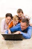 Familj av fyra som ligger, och den seende bärbar dator Arkivfoton