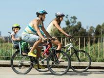 Familj av fyra som reser med cyklar Arkivbild
