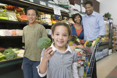 Familj av fyra som shoppar i supermarket Royaltyfria Foton