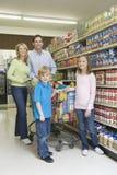 Familj av fyra som shoppar i supermarket Arkivfoto