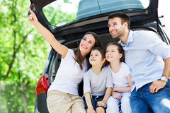 Familj av fyra som sitter i bilstam Arkivbilder
