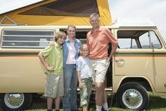 Familj av fyra som står vid Campervan Royaltyfri Foto