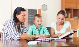 Familj av görande läxa tre i hem Royaltyfri Fotografi