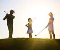 Familj av golfare på solnedgången Royaltyfri Bild