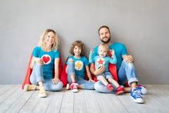 Familj av superheroes som hemma spelar arkivfoto