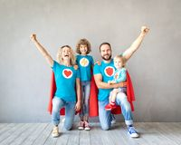Familj av superheroes som hemma spelar royaltyfri bild