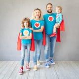 Familj av superheroes som hemma spelar royaltyfria foton