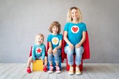 Familj av superheroes som hemma spelar royaltyfri foto