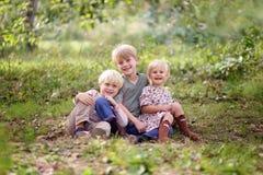 Familj av tre lyckliga unga barn som poserar yttersidan i skog Royaltyfria Bilder