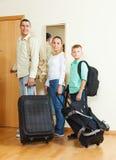 Familj av tre med bagage som går på ferie Arkivfoto