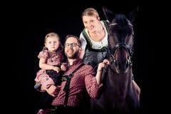 Familj av tre med deras häst Arkivfoto