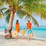 Familj av tre p? stranden under palmtr?det arkivbild