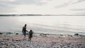 Familj av tre personer som går på en strand Moder, dotter och son som går att bevattna och att rymma händer stock video
