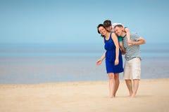 Familj av tre som har gyckel på tropisk strand Royaltyfri Foto