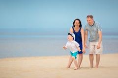 Familj av tre som har gyckel på tropisk strand Royaltyfria Foton