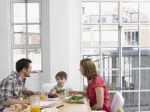 Familj av tre som har mål på att äta middag tabellen Arkivfoto