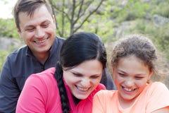 Familj av tre som skrattar i berget royaltyfri bild