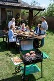Familj av tre utvecklingar som äter och dricker på tabellen, medan grilla kött utomhus Royaltyfri Fotografi