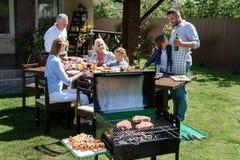 Familj av tre utvecklingar som äter och dricker på tabellen, medan grilla kött utomhus Royaltyfri Foto