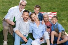 Familj av tre utvecklingar som tillsammans sitter på grön gräsmatta och ler på kameran Royaltyfri Bild