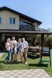 Familj av tre utvecklingar som tillsammans står på grön gräsmatta och ler på kameran Royaltyfri Foto