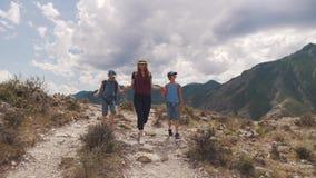 Familj av turister en ung kvinna med barn som promenerar en bana i bergen En ung moder och barn med lager videofilmer