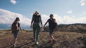 Familj av turister en ung kvinna med barn som promenerar en bana i bergen En ung moder och barn med stock video