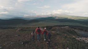 _ Familj av turister en ung kvinna och en man med barn som promenerar en bana i bergen En ung moder lager videofilmer