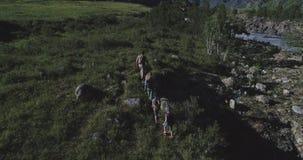 _ Familj av turister en ung kvinna och en man med barn som promenerar en bana i bergen En ung moder arkivfilmer