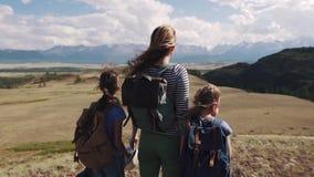 Familj av turister på en resa moder med två döttrar i aktionen barn med ryggsäckar beundrar sikten av lager videofilmer