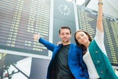 Familj av två i bakgrund för internationell flygplats informationsbrädet om flyg royaltyfri fotografi