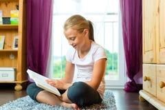 Familj - barn eller tonåring som läser en bok royaltyfria bilder