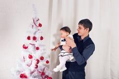 Familj barn, jul, x-mas, förälskelsebegrepp - den lyckliga fadern med förtjusande behandla som ett barn dottern nära julträd Royaltyfri Foto