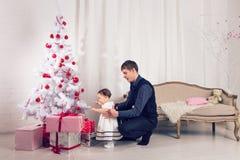 Familj barn, jul, x-mas, förälskelsebegrepp - den lyckliga fadern med förtjusande behandla som ett barn dottern nära julträd Arkivbilder