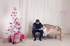 Familj barn, jul, x-mas, förälskelsebegrepp - den lyckliga fadern med förtjusande behandla som ett barn dottern nära julträd Fotografering för Bildbyråer