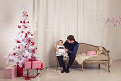 Familj barn, jul, x-mas, förälskelsebegrepp - den lyckliga fadern med förtjusande behandla som ett barn dottern nära julträd Royaltyfria Foton