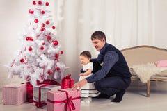 Familj barn, jul, x-mas, förälskelsebegrepp - den lyckliga fadern med förtjusande behandla som ett barn dottern nära julträd Royaltyfria Bilder