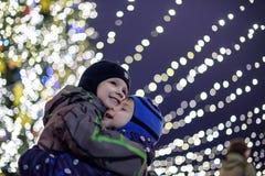 Familj, barndom, säsong och folkbegrepp - som är lyckligt i vinterkläder över snöig stadsbakgrund Fotografering för Bildbyråer