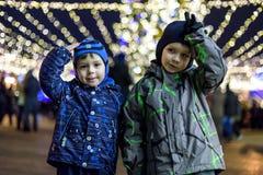 Familj, barndom, säsong och folkbegrepp - som är lyckligt i vinterkläder över snöig stadsbakgrund Arkivbilder