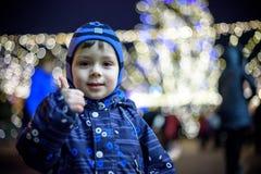 Familj, barndom, säsong och folkbegrepp - som är lyckligt i vinterkläder över snöig stadsbakgrund Arkivfoto