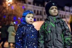 Familj, barndom, säsong och folkbegrepp - som är lyckligt i vinterkläder över snöig stadsbakgrund Arkivfoton