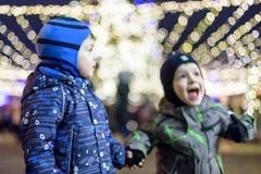 Familj, barndom, säsong och folkbegrepp - som är lyckligt i vinterkläder över snöig stadsbakgrund Royaltyfri Foto