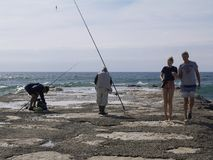 Familj bredvid fiskare i stranden royaltyfri foto