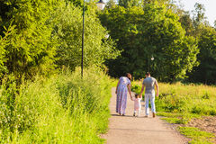 Familj, föräldraskap och folkbegrepp - den lyckliga modern, fadern och lilla flickan som går i sommar, parkerar Royaltyfria Foton