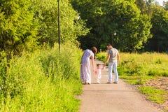 Familj, föräldraskap och folkbegrepp - den lyckliga modern, fadern och lilla flickan som går i sommar, parkerar Arkivbild