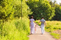 Familj, föräldraskap och folkbegrepp - den lyckliga modern, fadern och lilla flickan som går i sommar, parkerar Royaltyfri Foto