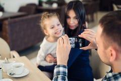 Familj föräldraskap, teknologi, folkbegrepp - lycklig fader som tar fotoet av hans lilla dotter och fru vid smartphonen arkivfoto