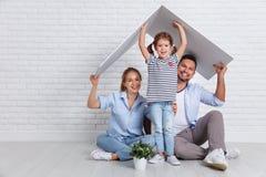 Familj för begreppshusbarn Moderfader och barn i nytt H arkivbilder